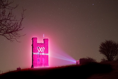 Broadway tower lit up pink with projection